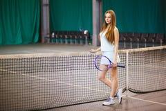 Retrato del jugador de tenis de la chica joven en un campo de tenis interior Fotografía de archivo
