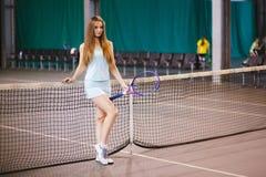 Retrato del jugador de tenis de la chica joven en un campo de tenis interior Imágenes de archivo libres de regalías