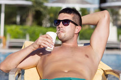 Retrato del jugo de consumición hermoso del hombre joven en la piscina Fotos de archivo