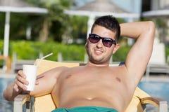 Retrato del jugo de consumición hermoso del hombre joven en la piscina Imagen de archivo