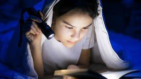 Retrato del libro de lectura del adolescente con la linterna en la noche Imagen de archivo