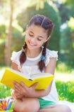 Retrato del libro de lectura bonito de la chica joven en parque Fotografía de archivo libre de regalías