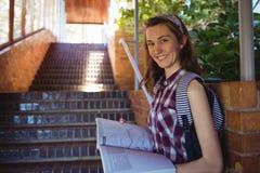 Retrato del libro de lectura de la colegiala cerca de la escalera Imagen de archivo