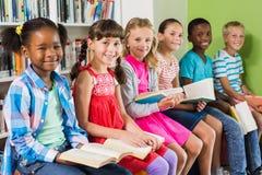 Retrato del libro de lectura de los niños en biblioteca imagenes de archivo
