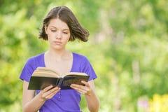 Retrato del libro de lectura de risa joven de la mujer Foto de archivo libre de regalías
