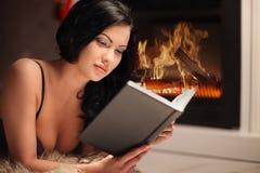 Retrato del libro de lectura hermoso de la mujer por la chimenea Fotografía de archivo