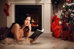 Retrato del libro de lectura hermoso de la mujer por la chimenea Imagenes de archivo