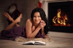 Retrato del libro de lectura hermoso de la mujer por la chimenea Imagen de archivo