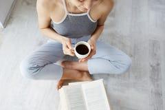 Retrato del libro de lectura hermoso joven blando de la muchacha que sostiene la taza de café que se sienta en piso sobre la pare Imágenes de archivo libres de regalías