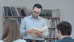 Retrato del libro de lectura joven del profesor en la sala de clase Fotografía de archivo libre de regalías