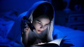 Retrato del libro de lectura de la muchacha en dormitorio oscuro con la linterna Fotografía de archivo