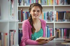 Retrato del libro de lectura sonriente de la colegiala en biblioteca Imagen de archivo libre de regalías