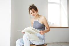 Retrato del libro de lectura sonriente de la muchacha feliz hermosa joven que se sienta en silla sobre la pared blanca en casa Imagen de archivo libre de regalías