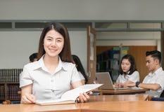 Retrato del libro de lectura sonriente lindo del estudiante Imagen de archivo libre de regalías