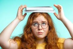Retrato del libro que lleva frustrado del adolescente en la cabeza aislada en azul Foto de archivo libre de regalías