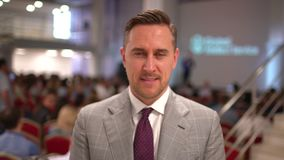 Retrato del locutor caucásico, hombre de negocios, líder empresarial acertado, directivo de la empresa en el fondo del almacen de metraje de vídeo