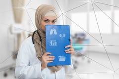Retrato del médico de sexo femenino musulmán preocupante que celebra el paperclip en el hospital Foto de archivo