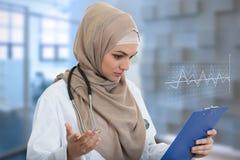 Retrato del médico de sexo femenino musulmán preocupante que sostiene el paperclip Foto de archivo