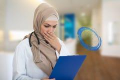 Retrato del médico de sexo femenino musulmán preocupante que sostiene el paperclip Foto de archivo libre de regalías