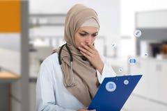 Retrato del médico de sexo femenino musulmán preocupante que sostiene el paperclip Imágenes de archivo libres de regalías