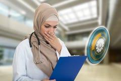 Retrato del médico de sexo femenino musulmán preocupante que sostiene el paperclip Fotos de archivo