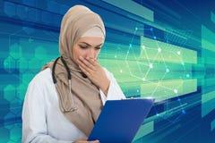 Retrato del médico de sexo femenino musulmán preocupante que sostiene el paperclip Imagen de archivo