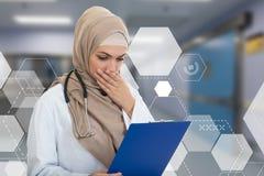 Retrato del médico de sexo femenino musulmán preocupante que sostiene el paperclip Imagen de archivo libre de regalías