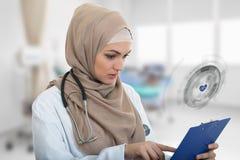 Retrato del médico de sexo femenino musulmán preocupante que sostiene el paperclip Fotografía de archivo