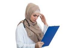 Retrato del médico de sexo femenino musulmán preocupante que sostiene el paperclip aislado Foto de archivo libre de regalías