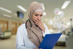 Retrato del médico de sexo femenino musulmán preocupante que sostiene el paperclip aislado Fotografía de archivo libre de regalías