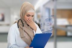 Retrato del médico de sexo femenino musulmán preocupante que sostiene el paperclip aislado Fotos de archivo