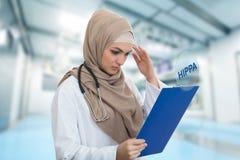 Retrato del médico de sexo femenino musulmán preocupante que sostiene el paperclip en hospital Imagenes de archivo