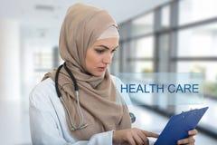 Retrato del médico de sexo femenino musulmán preocupante que sostiene el paperclip en hospital Fotografía de archivo