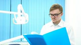 Retrato del médico que lee un documento en su oficina, concepto del informe de la medicina Jóvenes, doctor serio o dentista almacen de metraje de vídeo