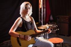 Retrato del músico de sexo femenino que toca la guitarra Foto de archivo libre de regalías
