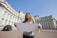 Retrato del mapa feliz de la tenencia de la mujer joven contra el arco del Ministerio de marina en Londres, Inglaterra, Reino Uni Fotos de archivo