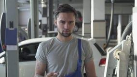 Retrato del mecánico de automóviles barbudo hermoso en el uniforme que hace girar una llave mientras que se coloca en servicio de almacen de metraje de vídeo