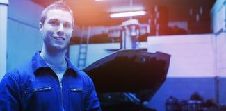Retrato del mecánico de sexo masculino con la tableta digital en el garaje imágenes de archivo libres de regalías