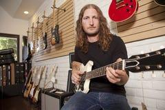 Retrato del mediados de hombre adulto serio que se sienta en tienda de la guitarra Foto de archivo