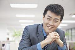 Retrato del mediados de hombre de negocios adulto sonriente Hands Clasped Imágenes de archivo libres de regalías