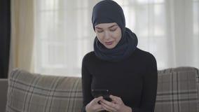Retrato del mensaje que mecanografía de la mujer musulmán joven independiente usando el smartphone que lleva el pañuelo tradicion metrajes