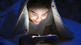 Retrato del mensaje que mecanografía sonriente de la muchacha hermosa en smartphone debajo de la manta en la noche Imágenes de archivo libres de regalías