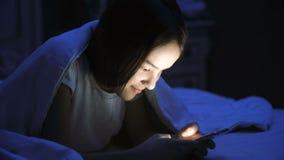 Retrato del mensaje que mecanografía sonriente hermoso de la muchacha en el teléfono móvil en la noche Fotos de archivo libres de regalías