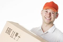 Retrato del mensajero de sexo masculino sonriente en casquillo anaranjado con la caja de cartón en las manos aisladas en el fondo imagen de archivo libre de regalías