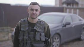 Retrato del militar valiente joven que permanece y que sonríe en la calle en uniforme en el fondo del coche metrajes