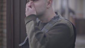 Retrato del militar valiente joven que va de la casa que trabaja al ejército en uniforme para proteger la patria almacen de metraje de vídeo