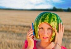 Retrato del modelo atractivo hermoso de la mujer joven con la sandía en la cabeza Imagen de archivo libre de regalías