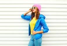 Retrato del modelo bonito de la mujer de la moda en la ropa colorida que presenta sobre el fondo blanco las gafas de sol rosadas  Fotos de archivo