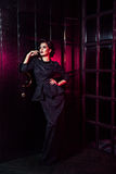 Retrato del modelo de moda hermoso en vestido negro clásico, maquillaje y peinado cerca de la situación y de la presentación oscu Fotos de archivo libres de regalías