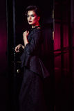 Retrato del modelo de moda hermoso en vestido negro clásico, maquillaje y peinado cerca de la situación y de la presentación oscu Imagenes de archivo
